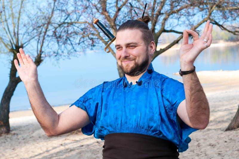 Przystojni uśmiechnięci samurajowie w błękitnym kimonie, pozycja śmia się medytację na plaży i pokazuje, zdjęcie royalty free