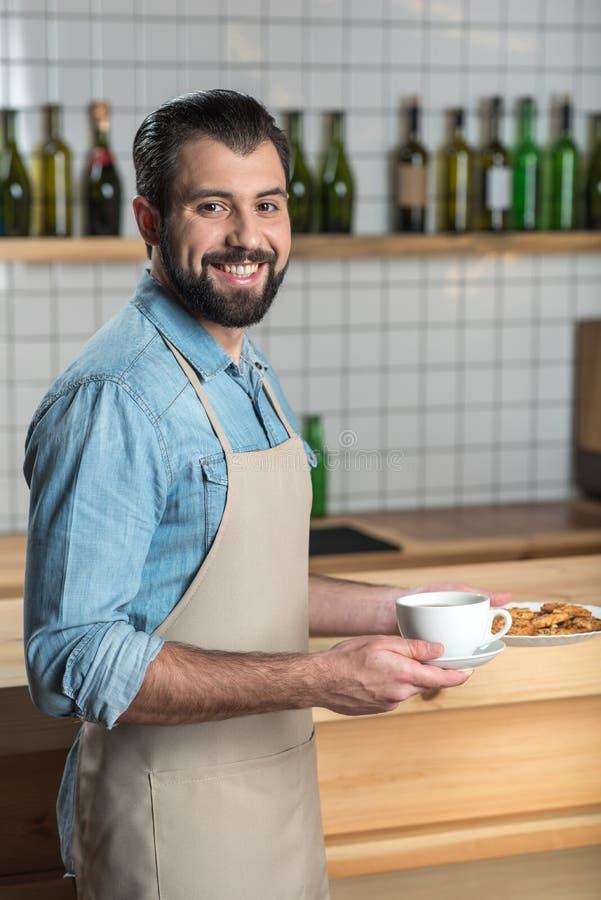 Przystojny życzliwy kelner ono uśmiecha się podczas gdy trzymający filiżankę kawy i ciastka zdjęcia royalty free