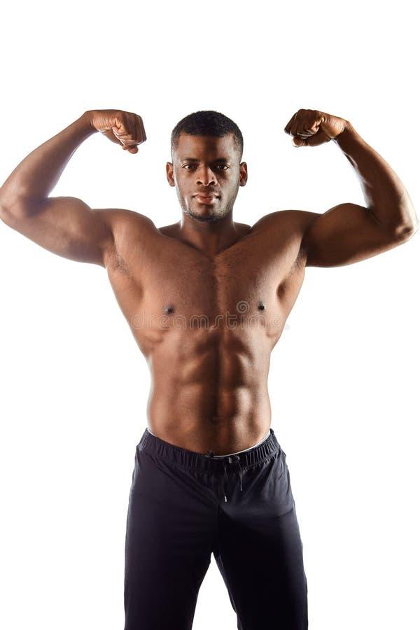 Przystojny afro mężczyzna pokazuje ciało i brzusznych mięśnie nad białym tłem fotografia royalty free