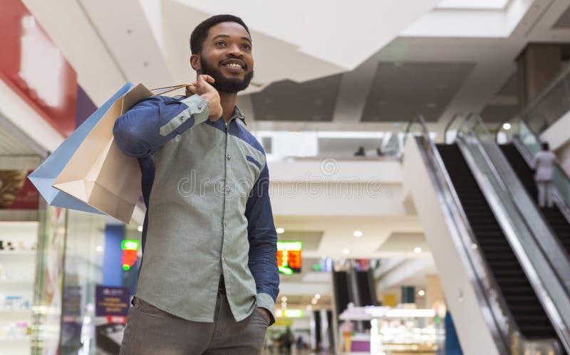 Przystojny afrykański mężczyzna czekać na dziewczyny z zakupami zdjęcia stock