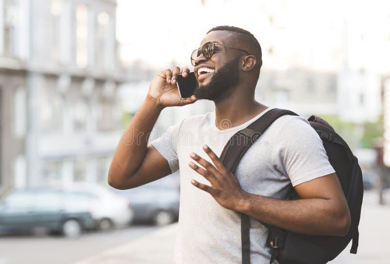 Przystojny afrykański mężczyzna negocjuje z przyjaciółmi z plecakiem fotografia stock