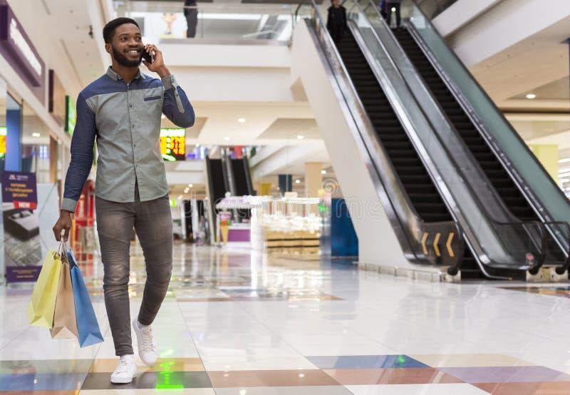 Przystojny afrykański mężczyzna opowiada telefonem komórkowym z torbami na zakupy zdjęcie stock
