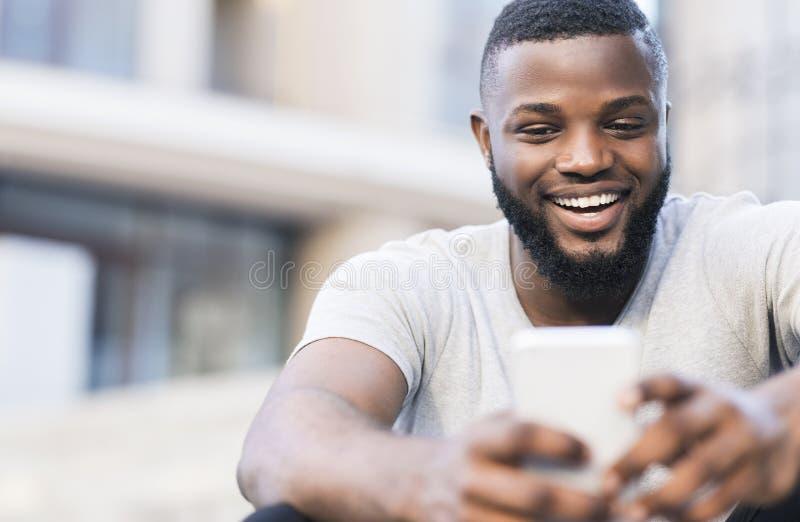 Przystojny afrykański mężczyzna robi selfie i ono uśmiecha się plenerowymi fotografia stock