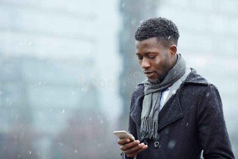 Przystojny Afrykański mężczyzna z Smartphone w śniegu zdjęcie stock