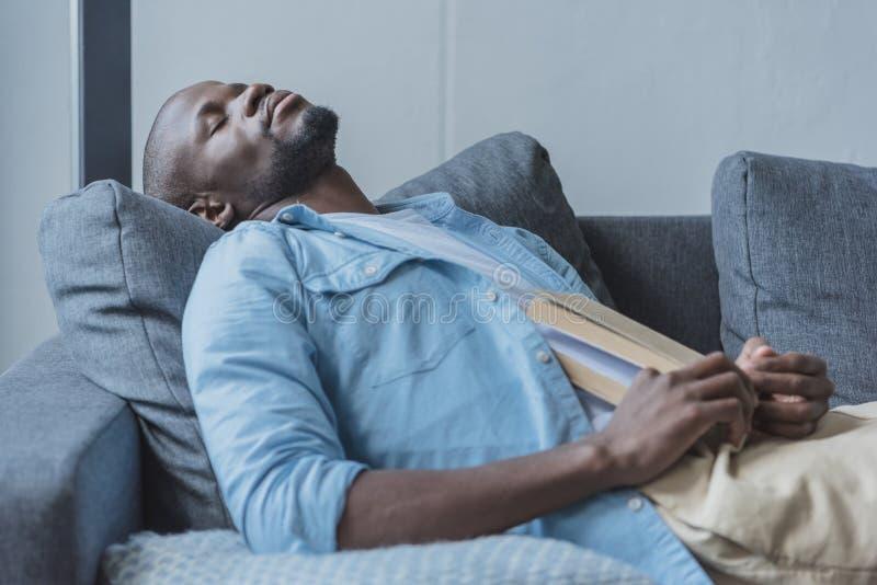Przystojny amerykanina afrykańskiego pochodzenia mężczyzna spadał uśpiony podczas gdy czytelnicza książka zdjęcia stock
