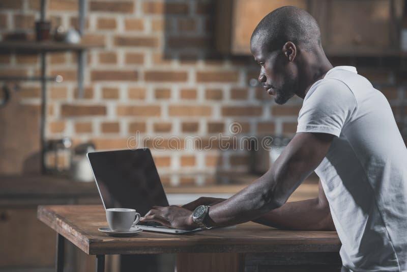 Przystojny amerykanina afrykańskiego pochodzenia mężczyzna używa laptop podczas śniadania zdjęcia royalty free