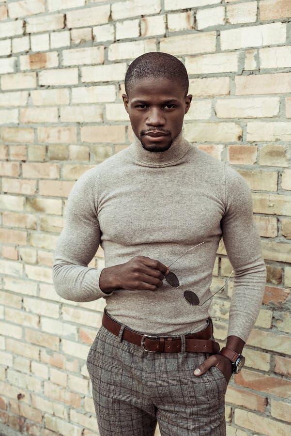 Przystojny amerykanina afrykańskiego pochodzenia mężczyzna w przypadkowych ubraniach pozuje przed ściana z cegieł i patrzeć obrazy stock