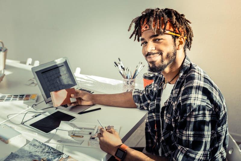Przystojny artysty czuć radosny podczas gdy pracujący w jego maluje studiu zdjęcia royalty free