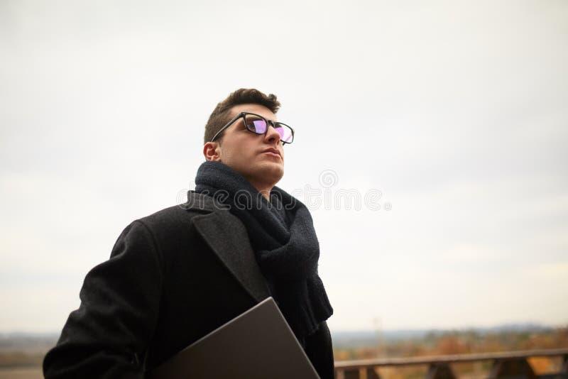Przystojny atrakcyjny biznesmen używa laptop na biuro tarasie Elegancki mężczyzna w szkłach żakiety dalej i szalik pozyci zdjęcie royalty free