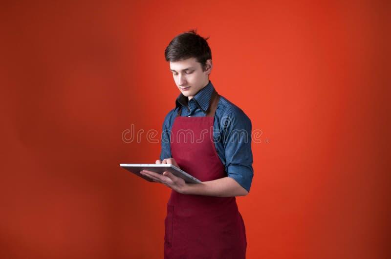 Przystojny barista z ciemnym włosy w Burgundy fartuchu używać cyfrową pastylkę na pomarańczowym tle zdjęcie royalty free