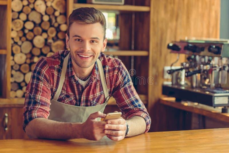 Przystojny barista z gadżetem zdjęcia stock