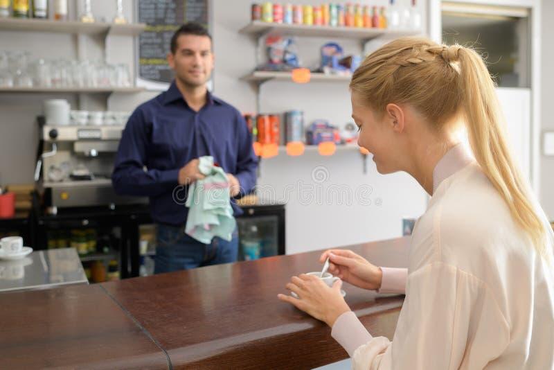 Przystojny barman flirtuje z ładnym klientem przy kawiarnią zdjęcie royalty free