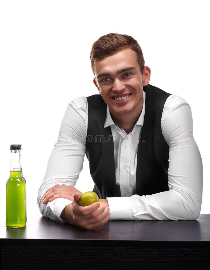 Przystojny barman przy prętowym kontuarem trzyma jaskrawego - zielony wapno na białym tle obraz stock