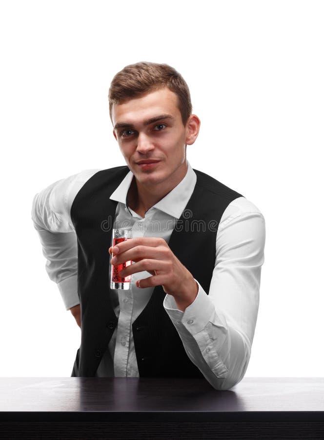 Przystojny barman przy prętowym kontuarem trzyma strzał odizolowywa na białym tle fotografia royalty free