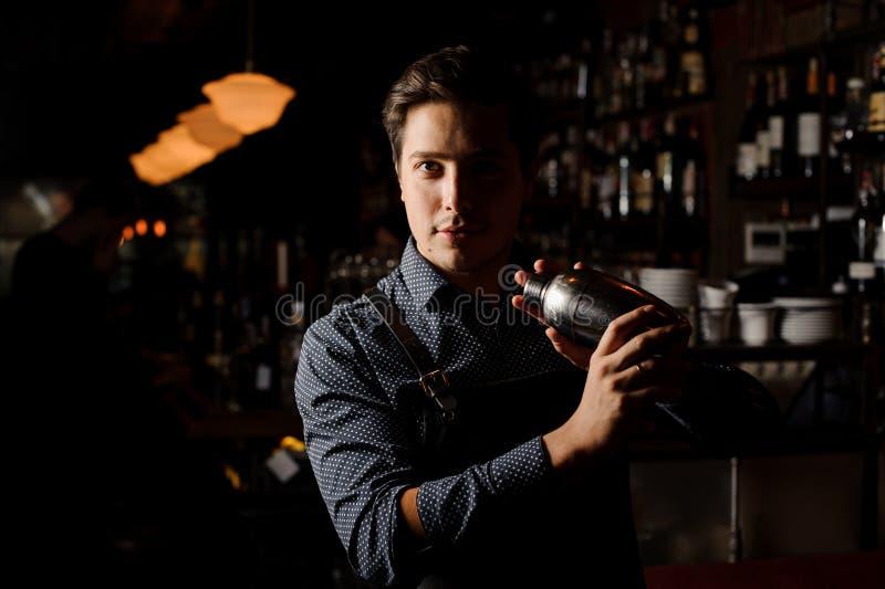 Przystojny barman trzyma potrząsacza w ciemnym barze zdjęcie royalty free