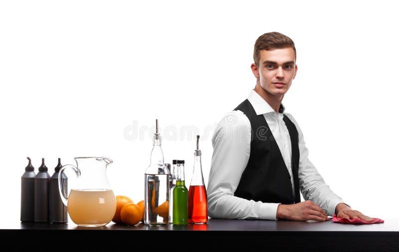 Przystojny barman wyciera prętowego kontuar, pomarańcze, butelki napoje na białym tle obraz royalty free