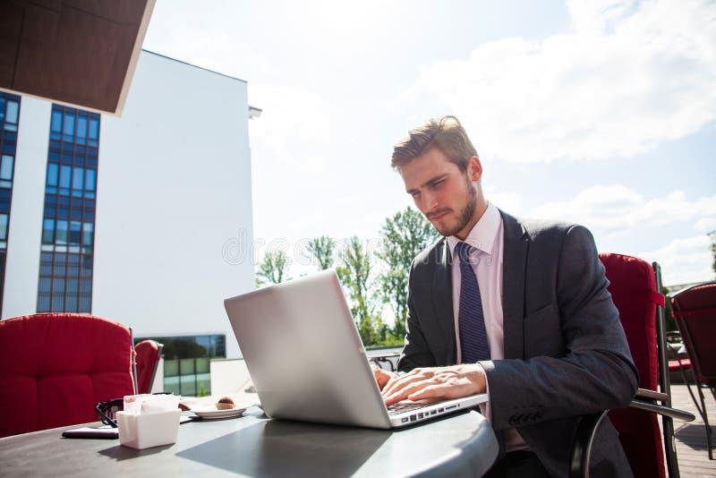 Przystojny biznesmen jest ubranym kostium i używa outdoors nowożytnego laptop, pomyślnego kierownika pracuje podczas przerwy, w k obrazy royalty free