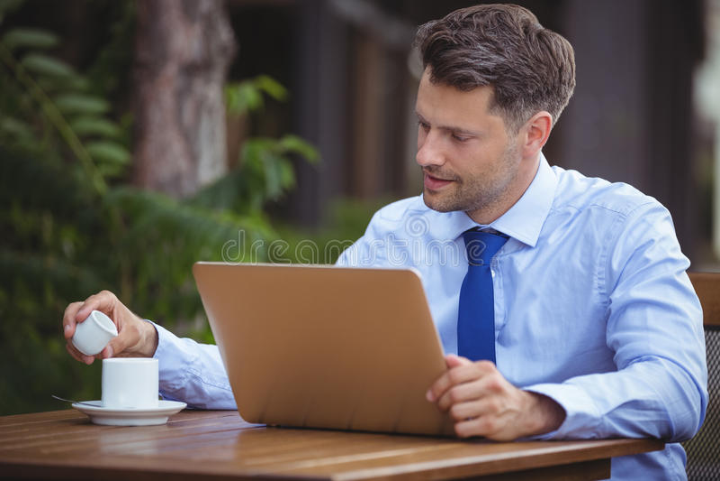 Przystojny biznesmen ma herbaty podczas gdy używać laptop zdjęcie stock
