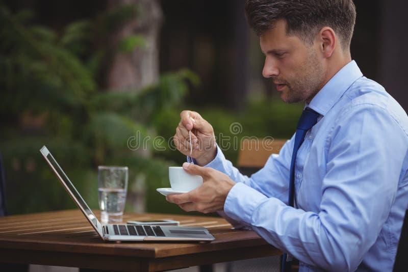 Przystojny biznesmen ma herbaty podczas gdy używać laptop zdjęcia royalty free