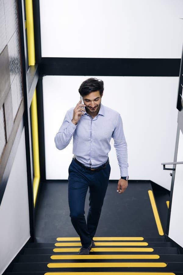 Przystojny biznesmen opowiada na telefonie komórkowym i pięciu na zdjęcia royalty free