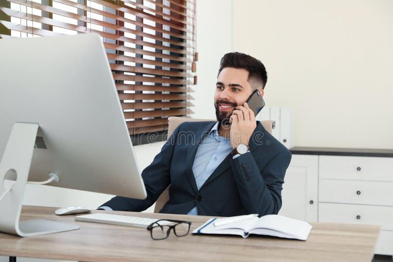 Przystojny biznesmen opowiada na telefonie podczas gdy pracujący z komputerem przy stołem fotografia stock