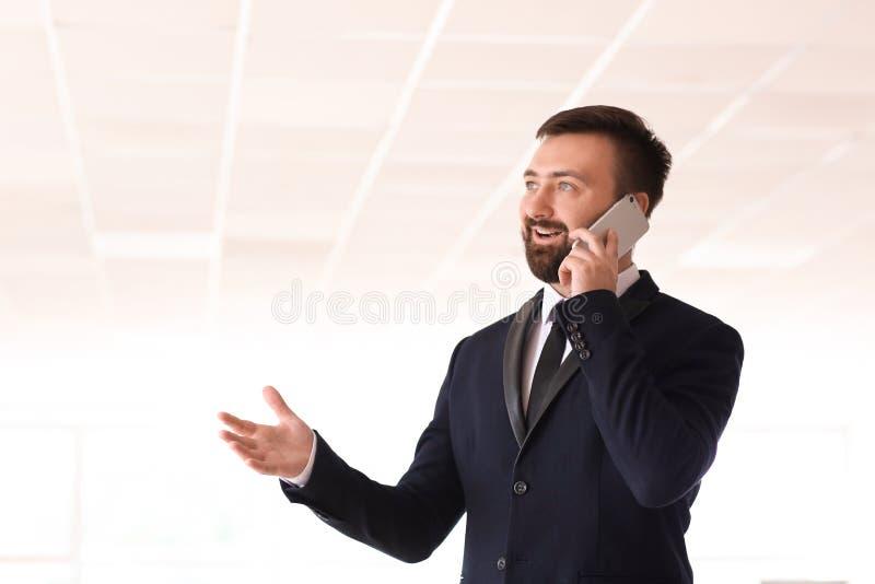 Przystojny biznesmen opowiada telefonem komórkowym w biurze zdjęcie royalty free