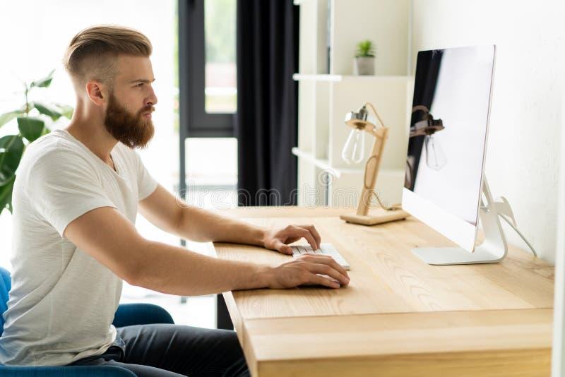 Przystojny biznesmen pracuje na komputerze w biurze zdjęcia stock