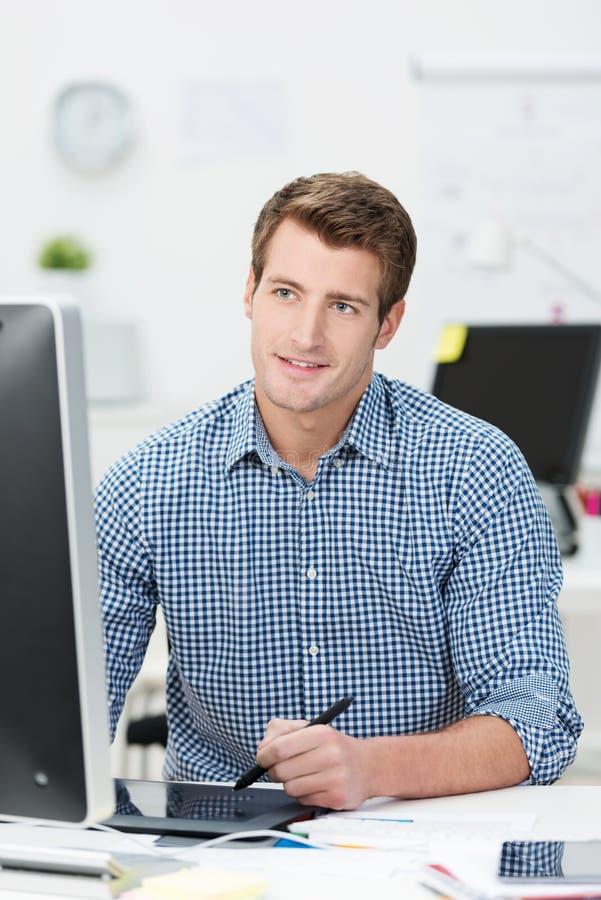 Przystojny biznesmen pracuje przy jego desktop obrazy royalty free