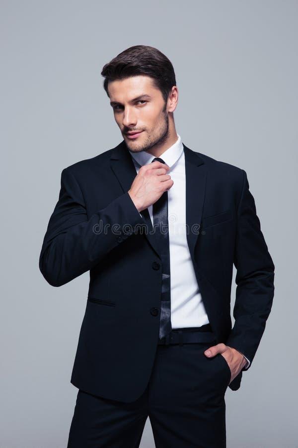 Przystojny biznesmen prostuje jego krawat zdjęcia stock