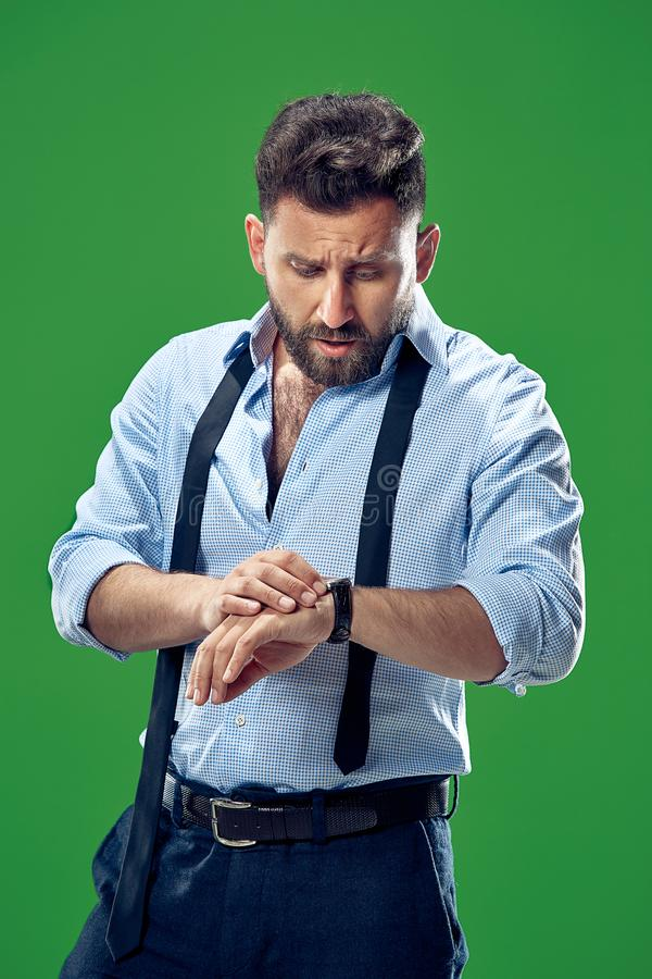 Przystojny biznesmen sprawdza jego wristwatch Odizolowywającego na białym tle obrazy stock