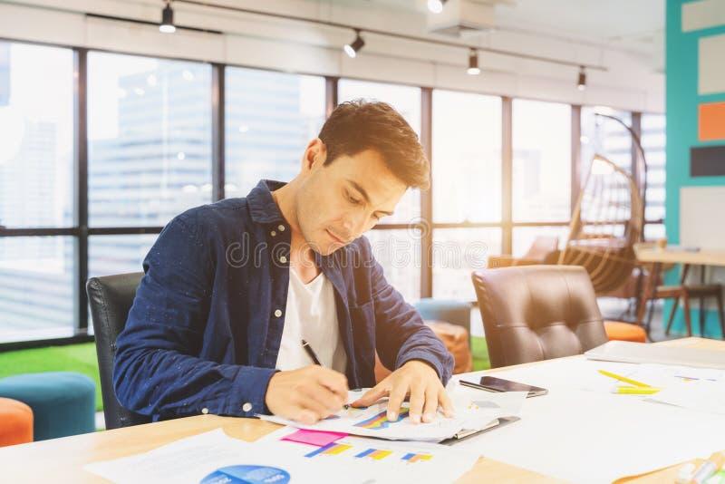 Przystojny biznesmen w eyeglasses robi notatkom i ono u?miecha si? podczas gdy pracuj?cy z laptopem w domu zdjęcie royalty free