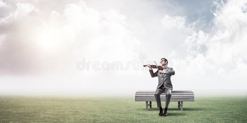 Przystojny biznesmen w parku na drewnianej ławki sztuce jego melodia zdjęcie stock