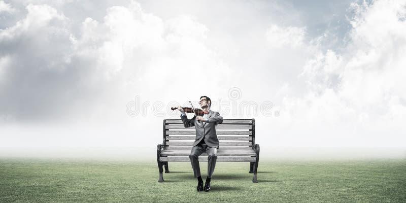Przystojny biznesmen w parku na drewnianej ławki sztuce jego melodia zdjęcia stock