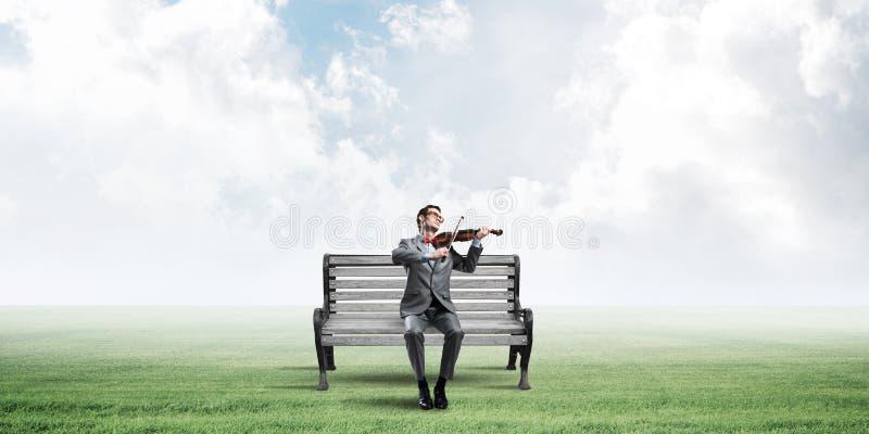 Przystojny biznesmen w parku na drewnianej ławki sztuce jego melodia obrazy stock