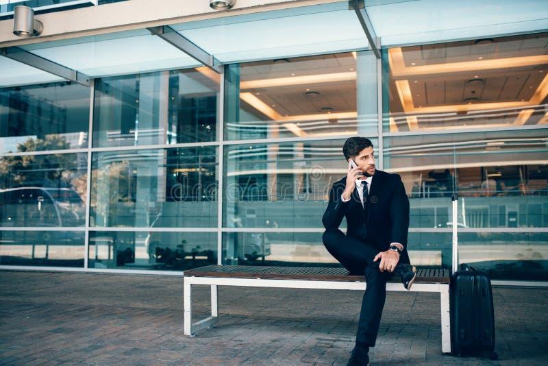 Przystojny biznesmena obsiadanie na ławce przy lotniskiem obraz royalty free