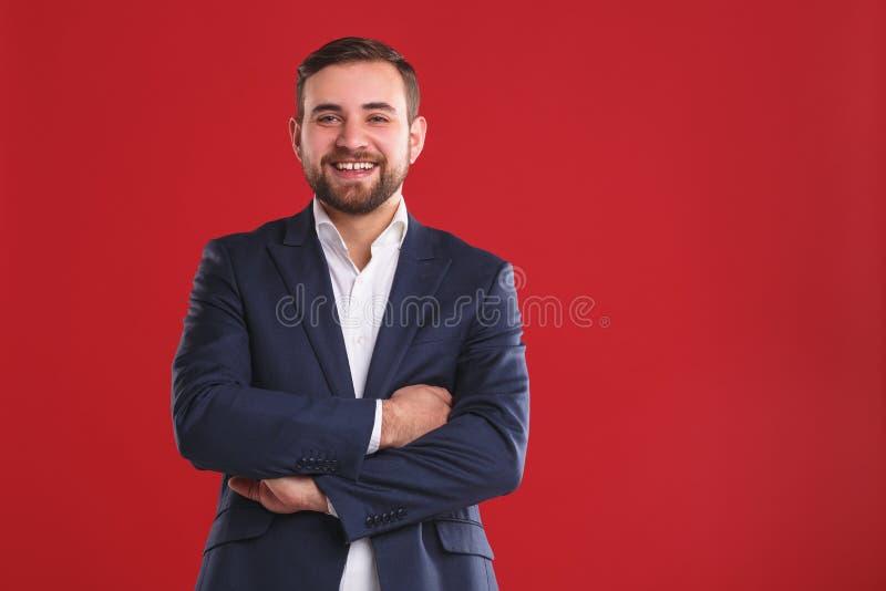 Przystojny biznesowy mężczyzna z brodą na czerwonym tle zdjęcia royalty free