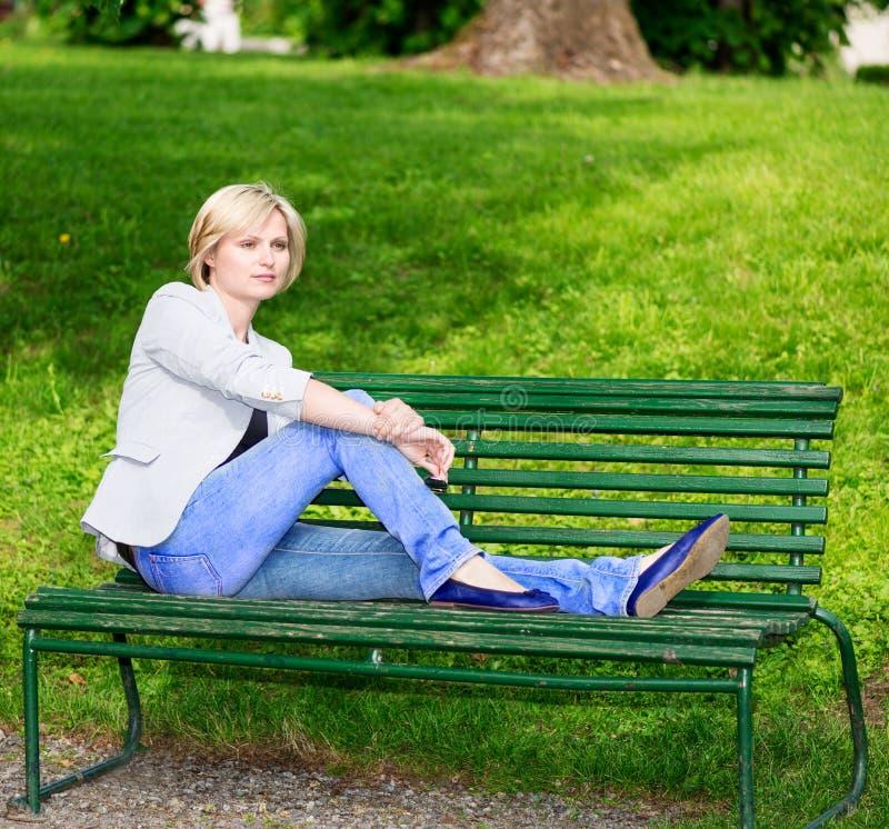 Przystojny blond kobiety obsiadanie na ławce zdjęcie royalty free