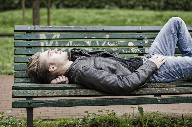 Przystojny blond młody człowiek kłaść na parkowej ławce fotografia royalty free