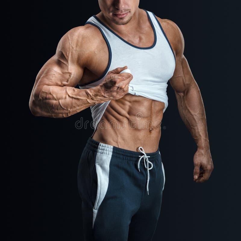 Przystojny bodybuilder z z wielką budową ciała pokazuje jego sześć paczek obraz royalty free