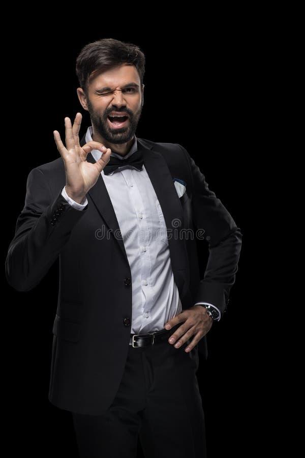 Przystojny brodaty biznesmen mruga ok znaka i pokazuje w łęku krawacie zdjęcie royalty free