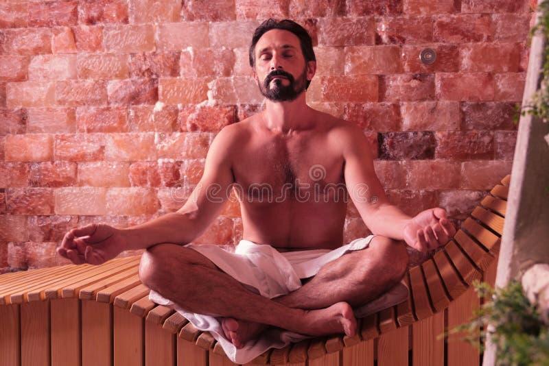 Przystojny brodaty mężczyzna medytuje w sauna zdjęcie stock