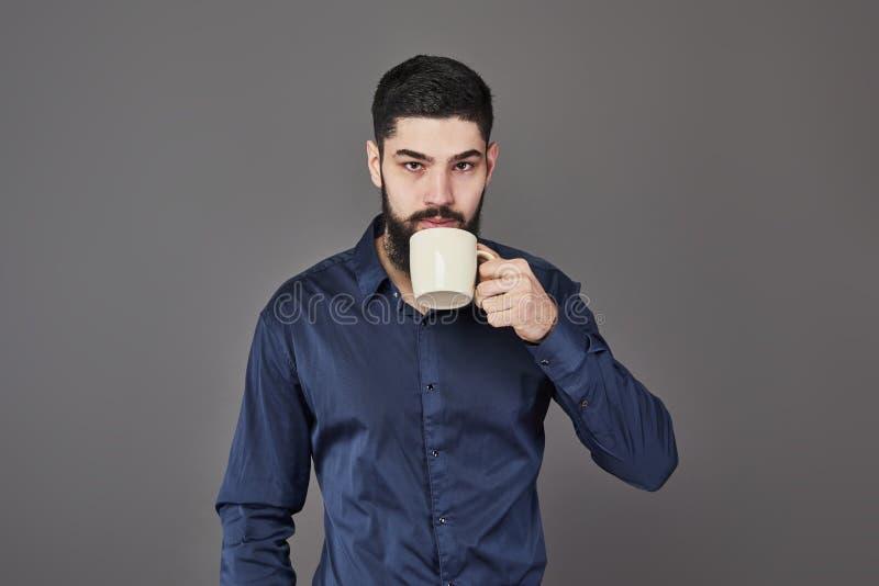 Przystojny brodaty mężczyzna pije herbaty z elegancką włosianą brodą i wąsy na poważnej twarzy w koszulowego mienia białej filiża zdjęcie stock