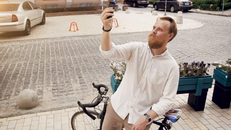 Przystojny brodaty mężczyzna robi selfie na rocznika bicyklu na ulicie fotografia royalty free