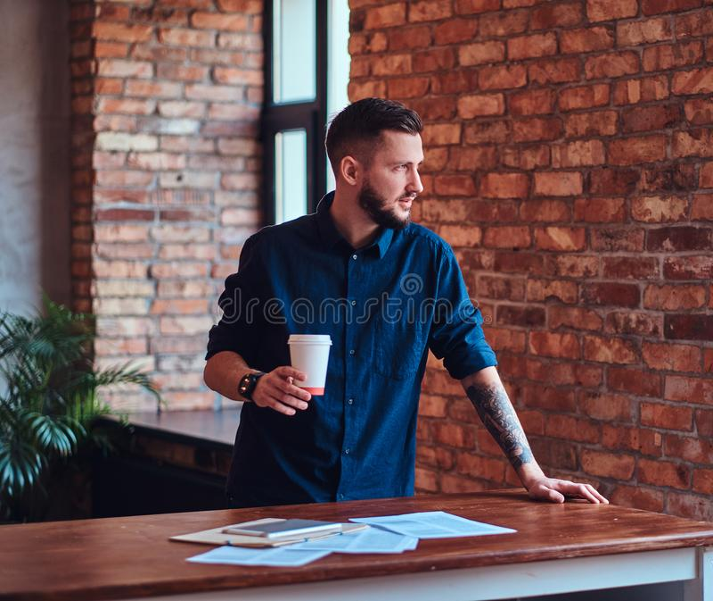 Przystojny brodaty mężczyzna trzyma takeaway działanie z papierowymi dokumentami w biurze z loft wnętrzem i kawę obraz royalty free