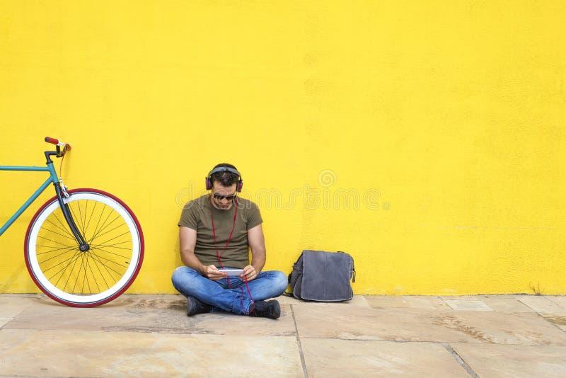 Przystojny brodaty mężczyzna używa telefon komórkowego w hełmofonach podczas gdy słuchający muzyka, wydaje czas z przyjemnością p obrazy royalty free