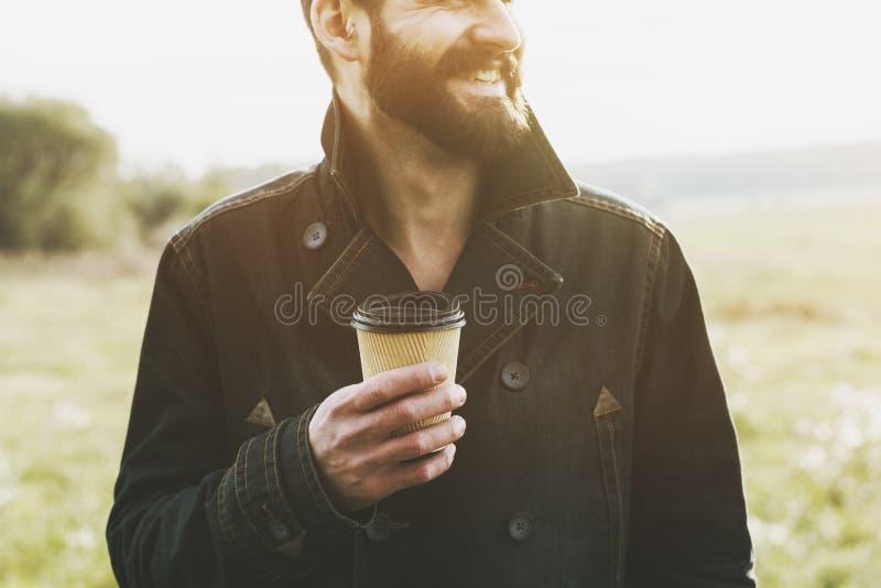 Przystojny brodaty mężczyzna z papierową filiżanką kawy zdjęcia royalty free