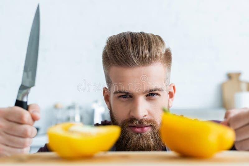 przystojny brodaty młodego człowieka mienia nóż i patrzeć połówki dzwon fotografia royalty free