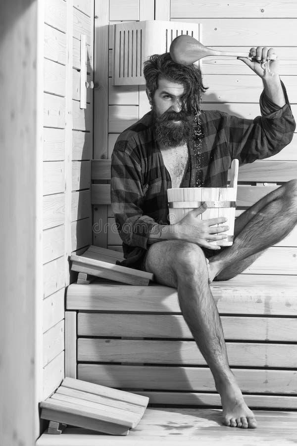 Przystojny brodaty uśmiechnięty mężczyzna w drewnianym skąpaniu z wiadrem fotografia royalty free