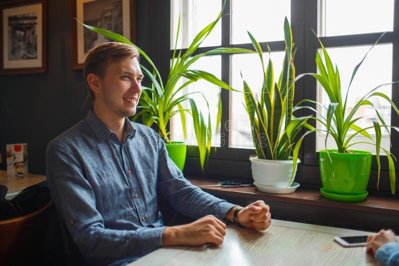 Przystojny brunetka mężczyzna ono uśmiecha się w kawiarni fotografia royalty free