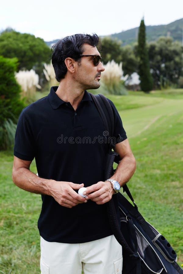 Przystojny brunetka mężczyzna w szkłach z golfową torbą na naramiennej mienie piłce w rękach zdjęcie royalty free